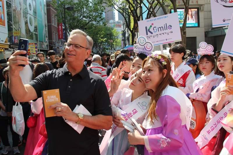 외국인 관광객에게 K스마일 캠페인을 알리고 있는 대학생 미소국가대표